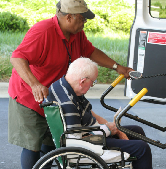 elder man on a wheelchair being pushed towards the car thru a ramp