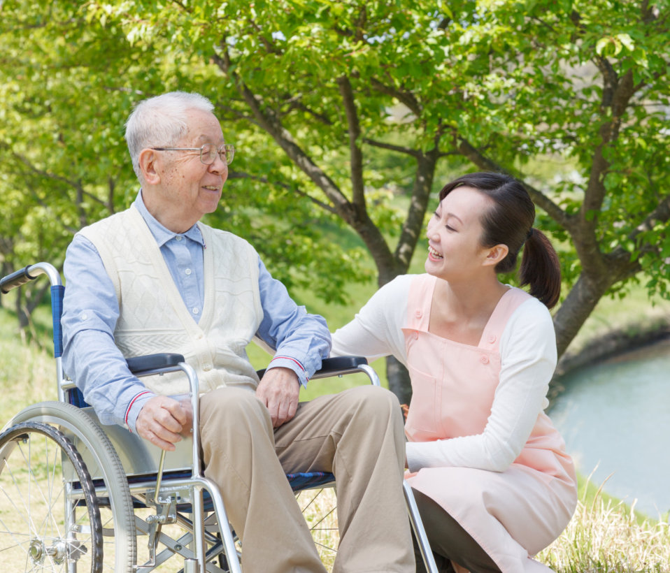 elder man sitting on a wheelchair with caregiver beside him